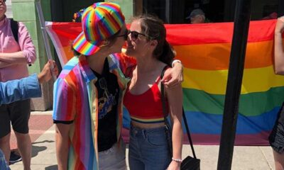 Two people hugging in front of a pride flag on the sidewalk