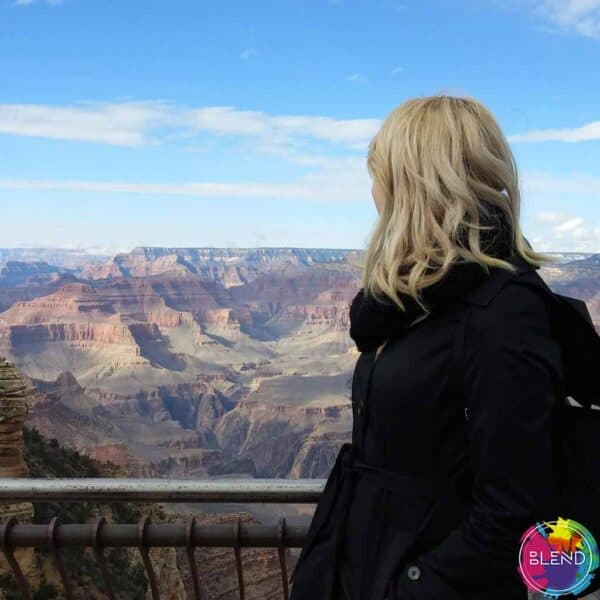 Author with blonde hair and black jacket staring over the Grand Canyon.