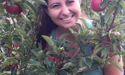 A girl with dark hair and blue tank top standing by an apple tree