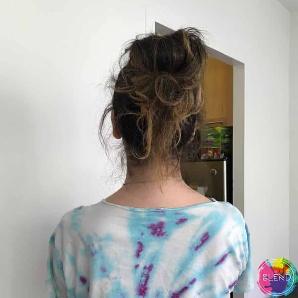 A girl with dark hair, blue and purple tie dye shirt facing away from the camera.