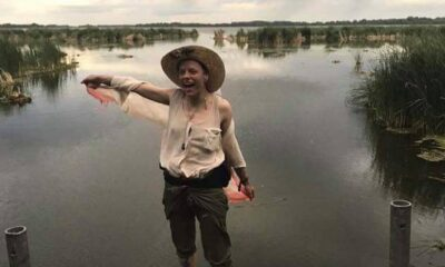 Author standing at the end of a dock with a straw hat, beige tank top and green pants smiling by a swamp.