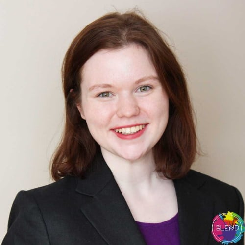 A redhead girl wearing a black blazer and a purple shirt, looking at camera, gray background..