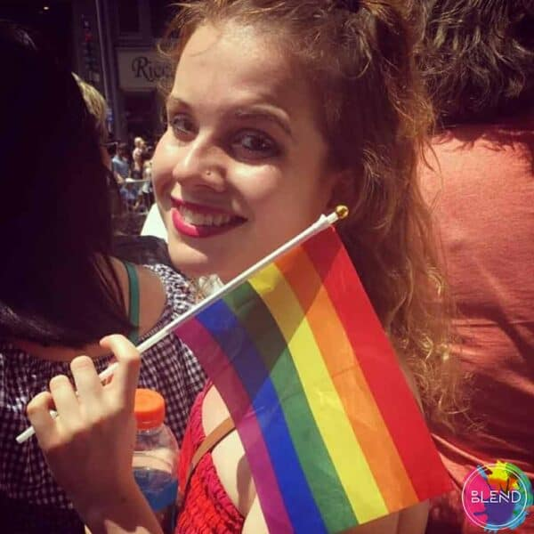 A girl with red hair and lipstick, holding a pride flag.