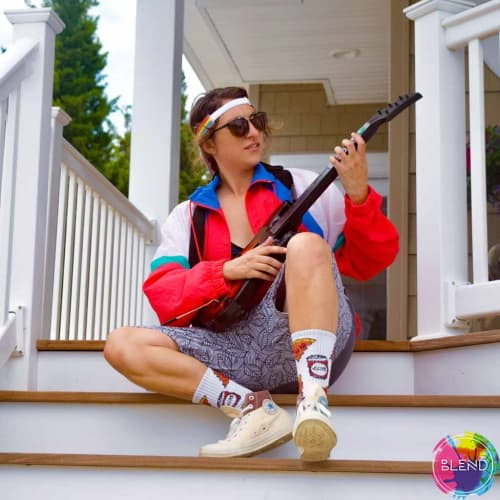 A brunette woman with short hair, sunglasses, and a rainbow headband plays her guitar outside her porch while wearing a red white and blue jacket with long white socks and shoes.