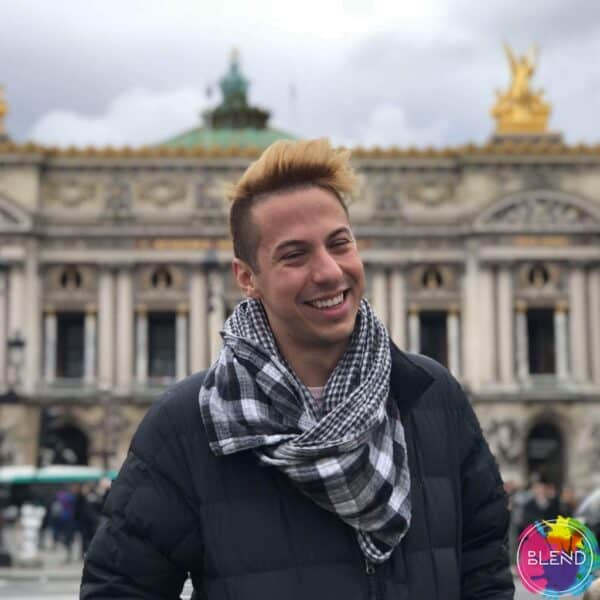 Author smiling and looking at the camera, wearing a black coat, white and gray scarf in front of a historical building