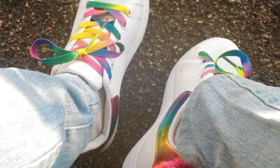 Two legs covered by jeans, a pair of white shoes with rainbow colored laces on top of the pavement