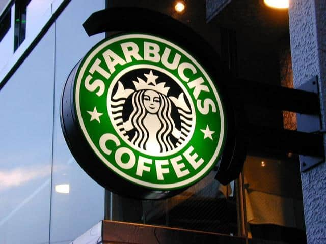 Starbucks Coffee logo on a window in front of a building.