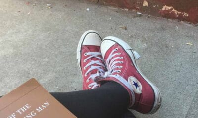 A person wearing red shoes with white laces and black slacks while sitting on the sidewalk reading a book outside.