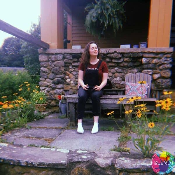 A girl with brown hair, wearing dark overalls, white socks and red shirt sitting on a bench outside a house next to flowers.