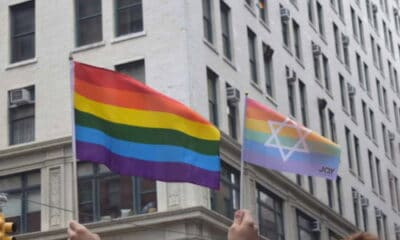 A person with short brown hair carrying the LGBTQ flag, carrying one with a Jewish symbol on it, outside of a building.