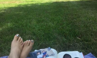 Legs crossed next to a book and sunglasses, on grass.