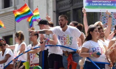 """Many men and women wearing a white """"pride and joy"""" T shirt with rainbow text on it, holding LGBTQ flags and signs."""