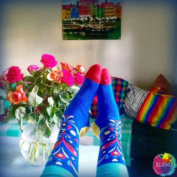A pair of feet in bright blue floral socks, in front of a jar of flowers, a couch with multiple multi colored and rainbow blankets, and a painting of a boat on a river way in front of several buildings.