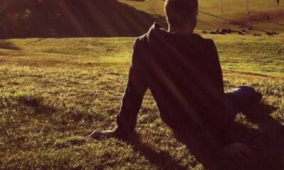 A man with short brown hair, wearing a jacket, sitting on the grass, outside in the sunset, with both of his arms stretched behind his back.