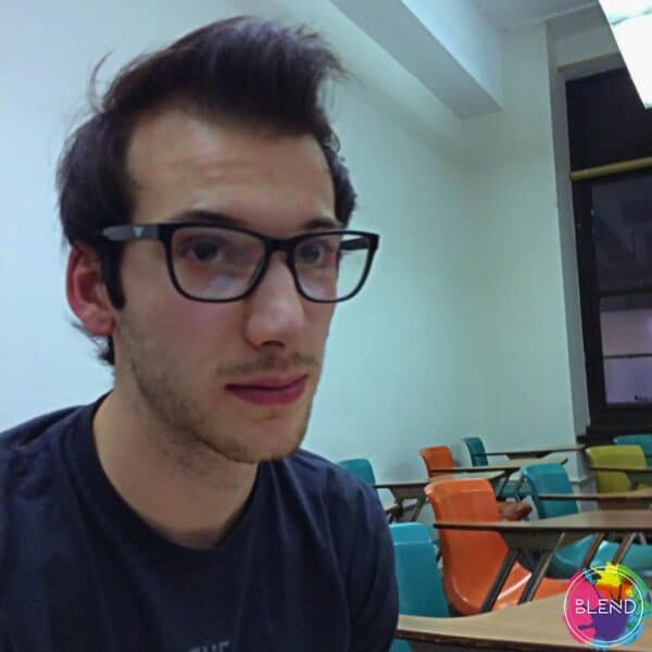 Author, brown wavy hairy, wearing glasses and a blue shirt in a classroom looking upwards and away from the camera