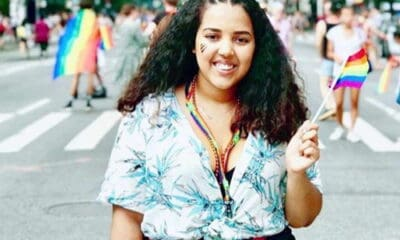 A girl with black curly hair, wearing a blue shirt and black slacks, with a red and white striped handbag, standing in the middle of the road at a pride parade.