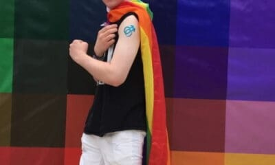 A young man with brown curly hair with sunglasses on and wearing a black shirt, white shorts, and a rainbow cape, standing in a room with rainbow square tiles in the background.
