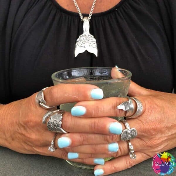 A women's hands with cyan painted nails and sliver jewelry on her fingers holding a glass cup.