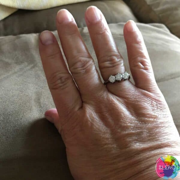 Authors hand laid comfortably on a piece of furniture with the focus on her beautiful wedding ring