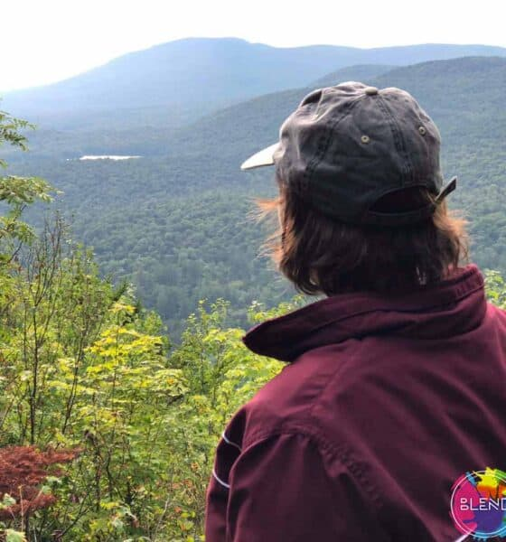 Author, in a maroon sweater, and grey cap in the mountains and overlooking a vast canopy of trees