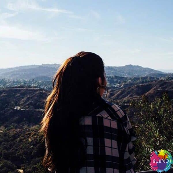 Author, dark brown hair, in a plaid shirt, sitting on top of a mountain looking at the vast landscape around her.