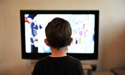 A little boy with brown hair, watching Netflix.