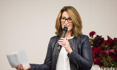 Adrienne Garland with brown short hair wearing glasses, a black jacket, and a grey top speaking on a microphone while holding a paper.