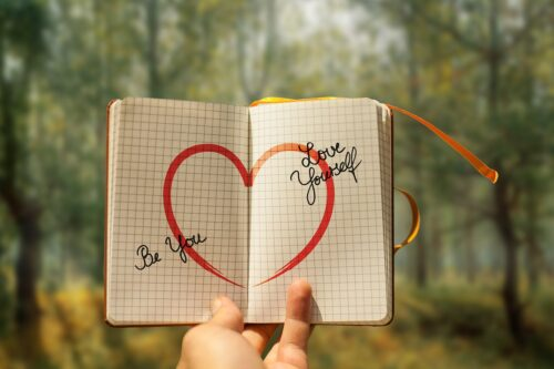 A person turning a book to a page with a red heart that says Love Yourself to the right of it, and,