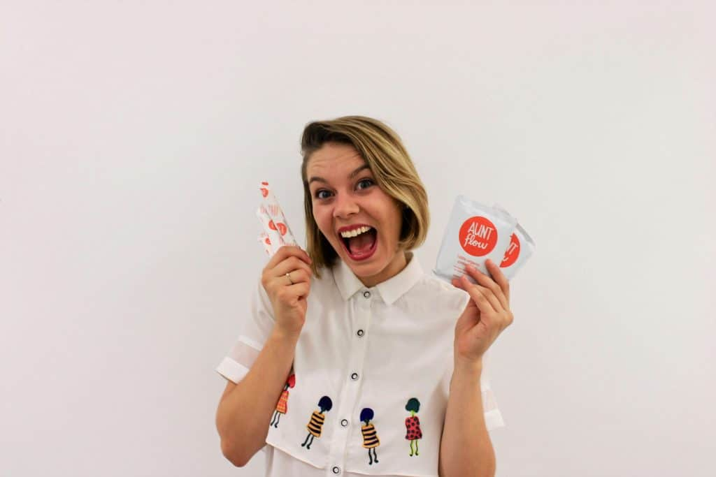 Claire Coder with blonde hair wearing a white polo shirt with buttons and drawings of women, while smiling and holding her Aunt Flow merchandise.