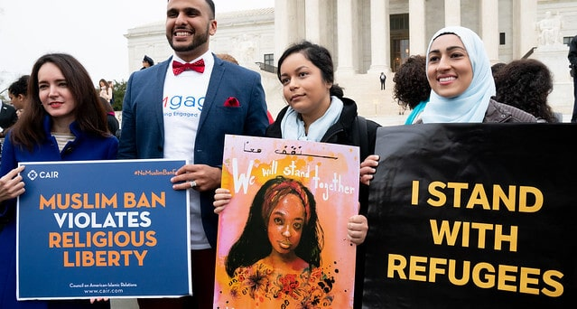 Protesters at the Travel Ban Rally hold signs in front of the Supreme Court