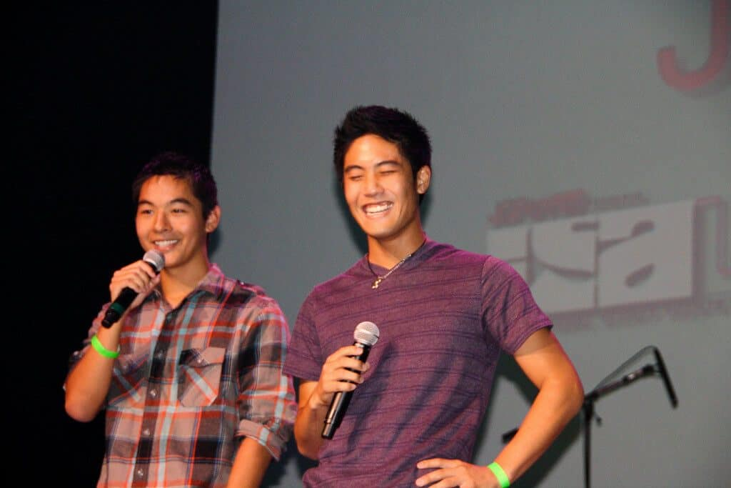 KevJumba and Niga Higa both smile and hold mics while they speak on stage