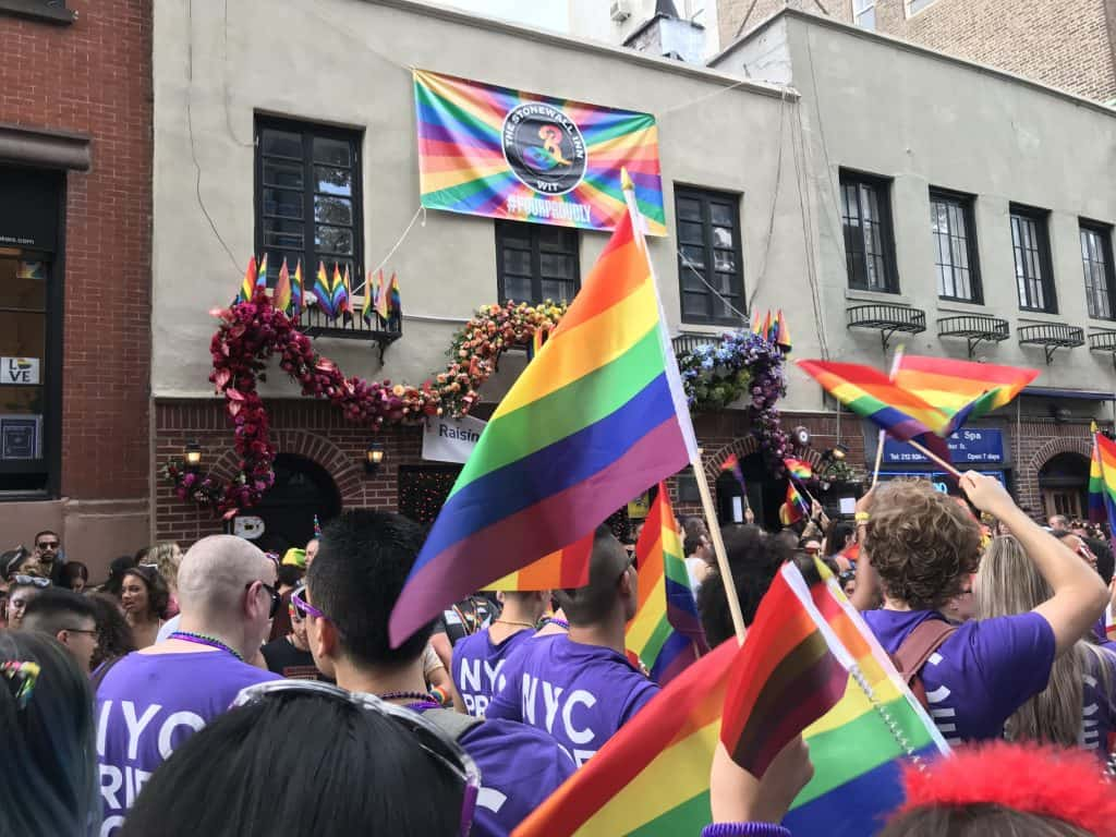 People march down the street holding rainbow colored flags.