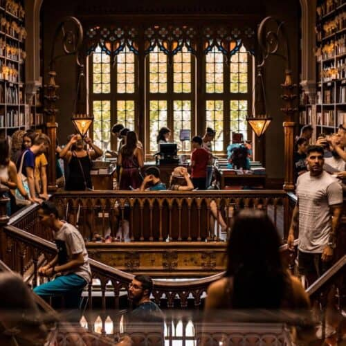 Lots of people studying upstairs in a big fancy brown wooden library.