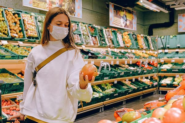 A young brunette lady wearing a white mask and white shirt picks out an orange at the grocery store.