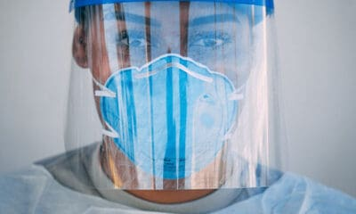 A lady in a blue facemask and a face shield wearing a grey shirt is one of many healthcare workers working hard to save lives.