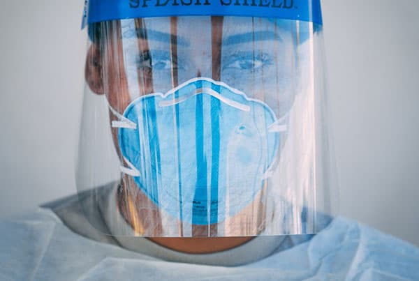 A lady in a blue facemask, and a blue face shield wearing a grey shirt, is one of many healthcare workers working hard to save lives.