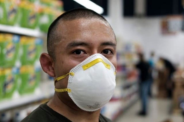 Man who is an essential worker with very short black hair and white facemask with yellow bands stands in front of paper towels in a commissary aisle.