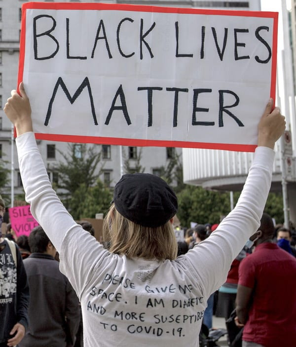 "A blond lady wearing a black hat and a long sleeved white shirt with black writing holding a big, ""BLACK LIVES MATTER"", sign, while standing outside at a rally."