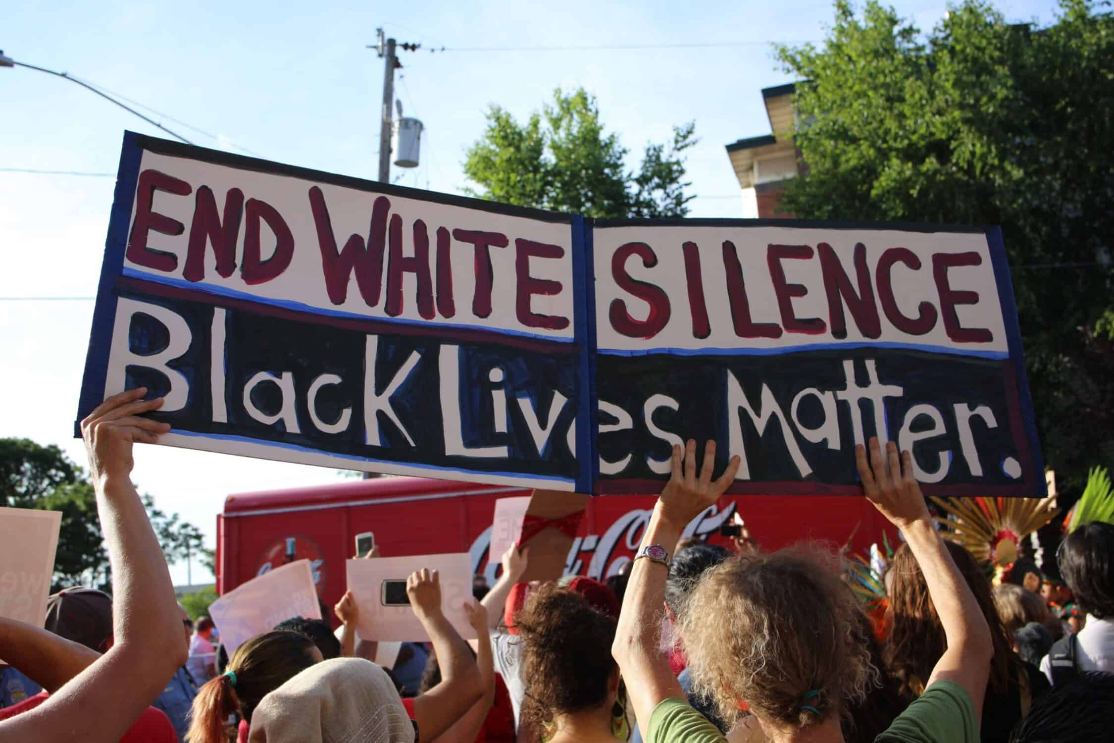 Protesters outside holding a blue, red, white and black sign that reads 'END WHITE SILENCE Black Lives Matter' at the Minneapolis protests.
