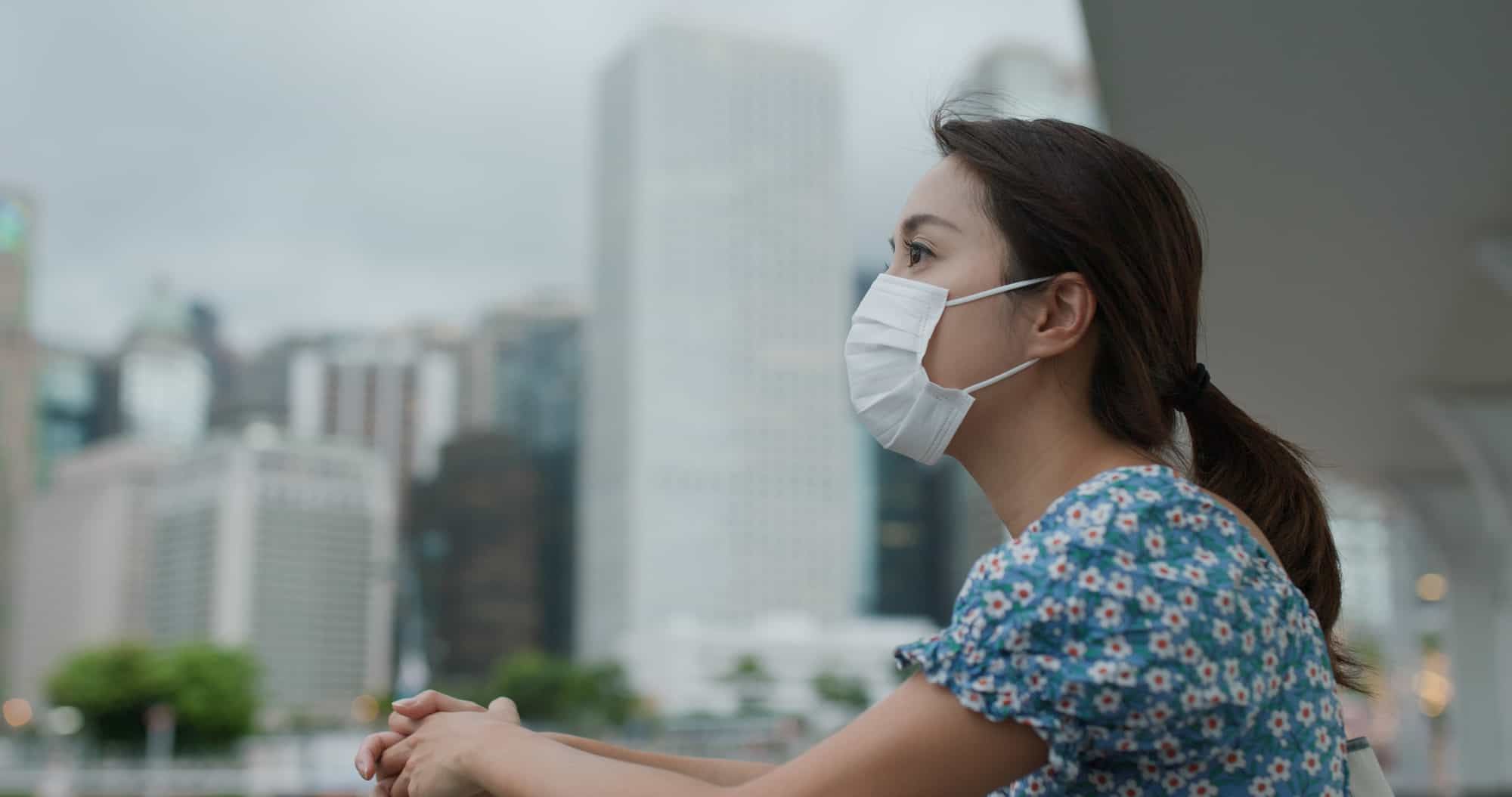A woman wearing a face mask looking left off a balcony.