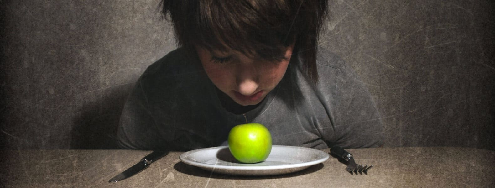 A girl with long hair wearing a gray shirt sitting at a table staring down at a green apple on a plate
