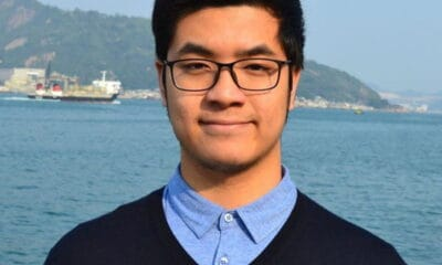 A young man with dark hair and glasses wearing a dark long sleeved shirt and a blue collared shirt stands outside at the pier.