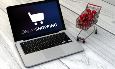 """A laptop placed on a wooden floor displaying a screen saying, """"Online Shopping"""", along with a miniature cart with presents on it."""
