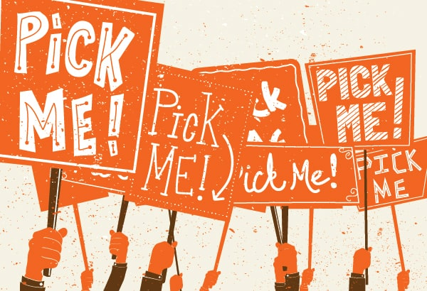 """Several hands with orange signs that say """"PICK ME"""" in white text."""