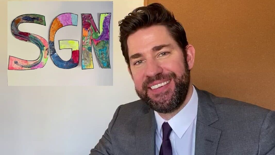 Actor John Krasinski wearing a grey suit smiling next to a sign that reads Some Good News