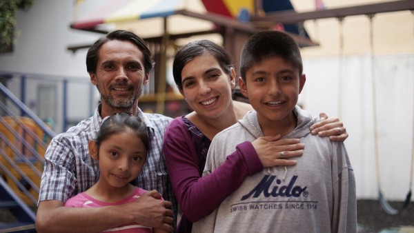 A picture of a hispanic family, all with dark hair, featuring a man in a beard and wearing a plaid shirt, a woman wearing a dark purple long-sleeved shirt, a little girl wearing a pink shirt, and a little boy wearing a grey sweater.
