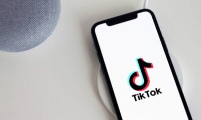 An iPhone showing the TikTok logo on a white screen, while placed on a grey counter.