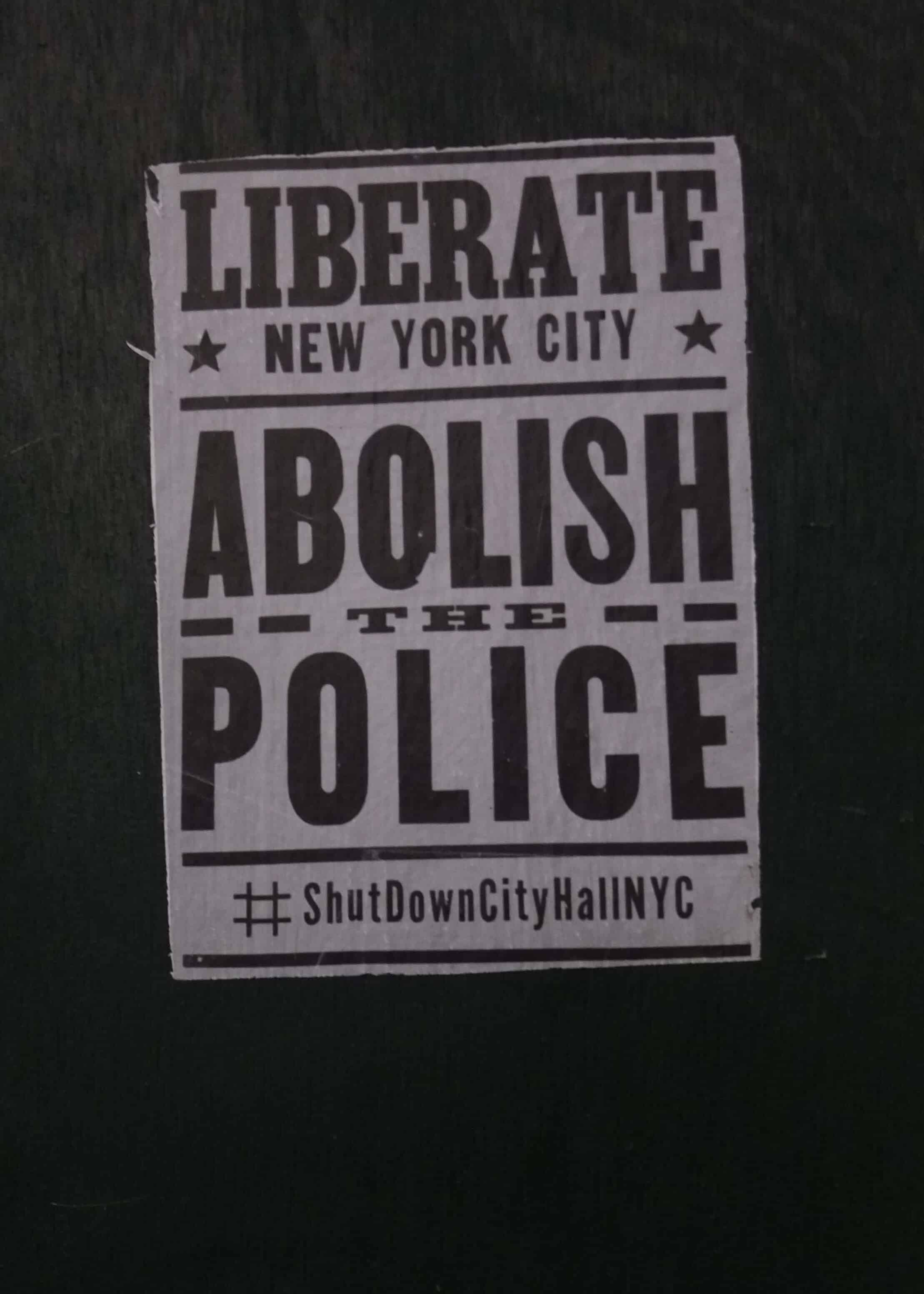 A sign on a black background that reads LIBERATE NEW YORK CITY, ABOLISH THE POLICE, #ShutDownCityHallNYC