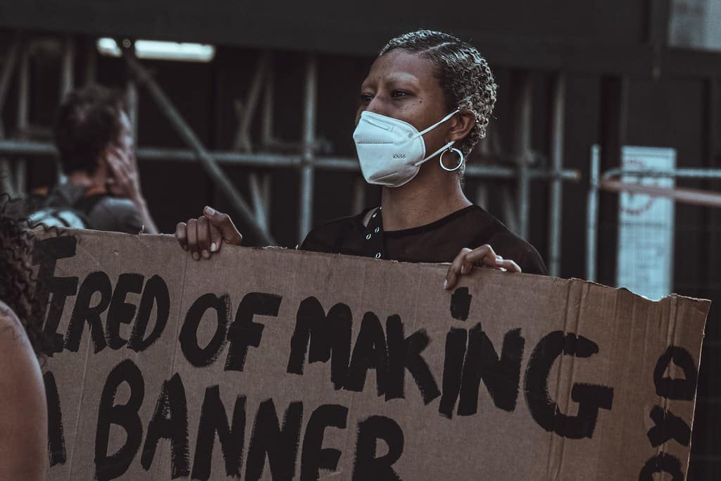 "An African American woman holding a sign that reads, ""Tired of making a banner."""