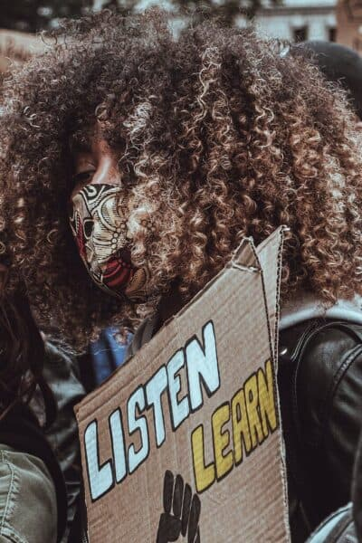 "A black women with brown curly hair, face mask and black jacket on, standing at a BLM protest holding a sign that says ""listen learn."""